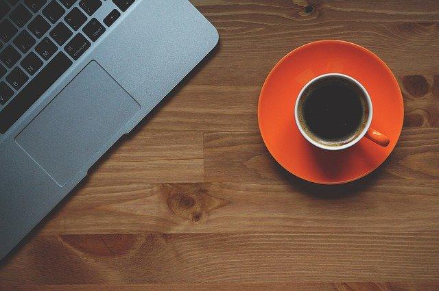 Laptop und rote Tasse mit Kaffee auf einem Holztisch: Wenn Sie schnell Geld benötigen, können Sie jetzt gleich den Targobank Sofortkredit bequem online beantragen!