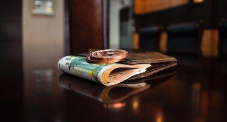 Geldbeutel mit mehreren 100 Euro Banknoten und zwei Münzen oben drauf: Seien Sie wieder flüssig, indem Sie sich einen günstigen 7000 Euro Kredit holen!