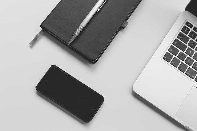 Smartphone, Notizbuch, Stift und Laptop auf einem Tisch: Wenn Sie gerade ein günstiges 120000 Euro Darlehen benötigen, dann können Sie heutzutage dank einem Online-Kreditvergleich einen überaus fairen 120000 Euro Kredit ausfindig machen!