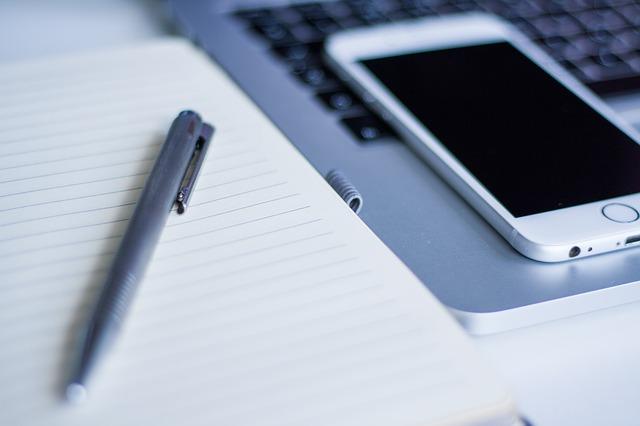 Notizblock, Stift, Smartphone und Laptop: Im digitalen Zeitalter ist es kein Problem mehr, einen volldigitalen Eilkredit komplett ohne Papierkram online aufzunehmen!