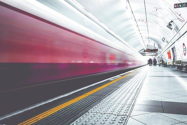 Roter Zug, der rasant an einer Haltestelle vorbeifährt: Wenn Sie gerade auf der Suche nach einem blitzschnellen Kredit sind, dann können Sie noch heute einen günstigen, volldigitalen Expresskredit mit Sofortauszahlung online beantragen!