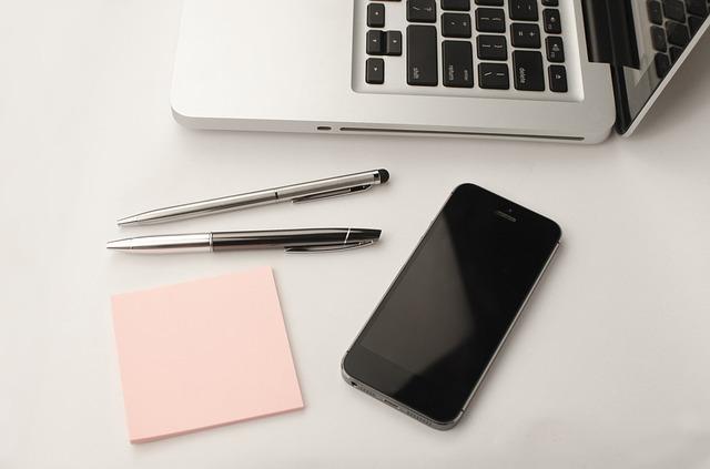 Notizzettel, Stifte, Smartphone und Laptop auf einem Schreibtisch: Sie benötigen schnellstmöglich einen fairen Kredit? Dann nehmen Sie noch heute einen günstigen volldigitalen Expresskredit mit Sofortauszahlung online auf!