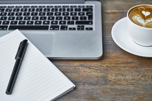 Notizbuch, Stift, Laptop und Tasse Kaffee auf einem Tisch: Wenn Sie gerade auf der Suche nach einem günstigen Kredit sind, dann schauen Sie sich am besten mal den HypoVereinsbank Kredit ab nur 1,59% eff. p.a. genauer an!