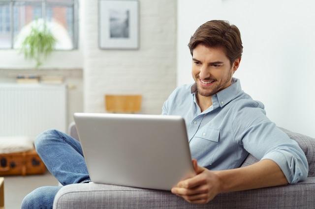 Junger Mann, der daheim auf seinem Sofa sitzt und gerade einen Kredit komplett online abschließen möchte!
