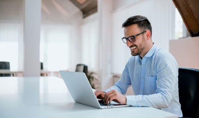 Junger Mann im Business-Hemd am Laptop sitzend: Die Digitalisierung hat es möglich gemacht, einen Kredit online unterschreiben und aufnehmen zu können - mit Hilfe der digitalen Unterschrift!