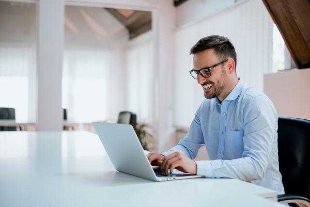 Junger Mann im Business-Hemd am Laptop sitzend: Die Digitalisierung hat es möglich gemacht, dass Verbraucherinnen und Verbraucher heute einen Kredit online unterschreiben und komplett papierlos aufnehmen können - mit Hilfe der digitalen Unterschrift!
