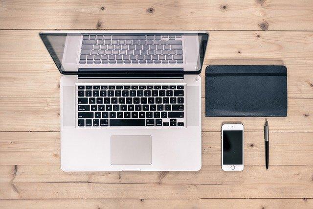 Laptop, Smartphone, Notizbuch und Stift auf einem hölzernen Schreibtisch: Wenn Sie gerade auf der Suche nach einem günstigen Sofortkredit mit volldigitaler Abwicklung sind, dann können Sie noch heute den Kredit2Day bzw. den solarisBank Kredit ab nur 0,68% eff. p.a. online beantragen!