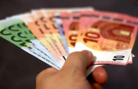 Hand mit mehreren 100-Euro, 50-Euro-, 20-Euro und 10-Euro-Banknoten: Wer schnell und unkompliziert Geld benötigt, kann im Leihhaus Hamm einen SCHUFA-freien Pfandkredit erhalten!