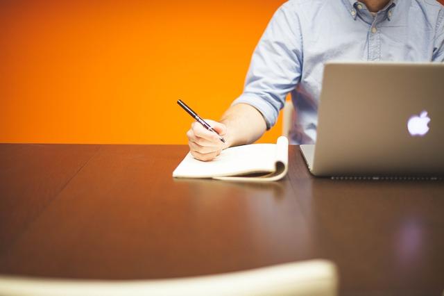 Junger Mann, am Schreibtisch vor seinem Laptop sitzend mit einem Stift in seiner rechten Hand: Wenn Sie gerade auf der Suche nach einem fairen Kredit sind, dann schauen Sie sich doch auch mal den norisbank Kredit ab nur 2,55% eff. p.a. genauer an!