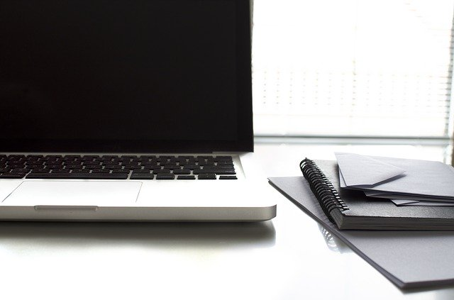 Laptop, Papier, Notizblock und Briefumschläge auf einem Schreibtisch: Wenn Sie einen fairen Kredit benötigen, dann können Sie noch heute den bonitätsunabhängigen PSD Bank Kredit ab nur 3,68% eff. p.a. online beantragen!