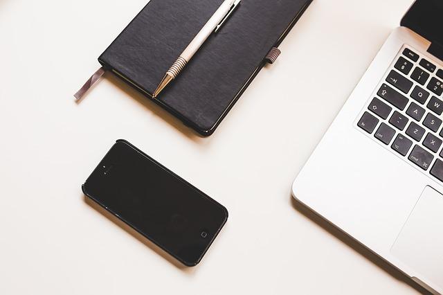 Smartphone, Notizbuch und Laptop auf einem weißen Tisch: Wenn Sie gerade auf der Suche nach einem günstigen Sofortkredit sind, dann können Sie noch heute den Qlick Kredit ab nur 1,48% eff. p.a. online beantragen!