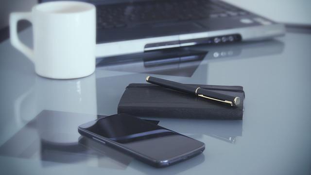 Smartphone, Notizbuch, Tasse und Laptop auf einem Tisch: Wenn Sie einfach und schnell Kredit bekommen möchten, dann können Sie noch heute einen volldigitalen Schnellkredit mit Sofortauszahlung online beantragen!