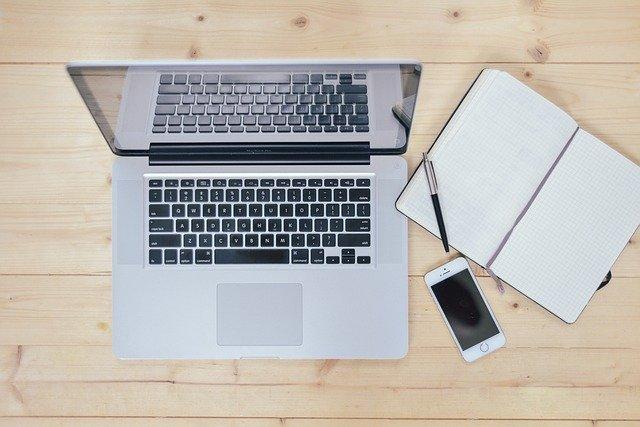 Laptop, Smartphone, Notizbuch und Stift auf einem Holztisch: Wenn Sie gerade auf der Suche nach einem fairen Kredit sind, dann können Sie noch heute den SKG Bank Kredit ab nur 2,19% eff. p.a. online beantragen!
