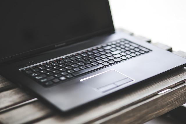 Schwarzer Laptop auf einem Holztisch: Wenn Sie auf der Suche nach einem fairen, bonitätsunabhängigen Kredit sind, dann sollten Sie sich mal den SKG Bank Ratenkredit genauer ansehen!
