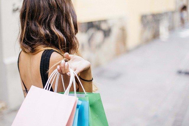 Glückliche Frau mit Einkaufstüten, die mit BNPL-Bezahlmethoden (Buy now, pay later) Waren eingekauft hat